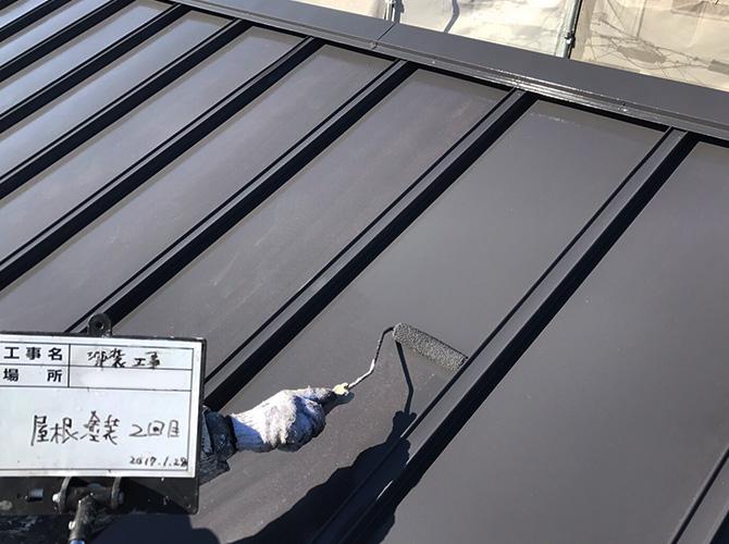 杉並区マンションの屋根塗装の上塗り施工中