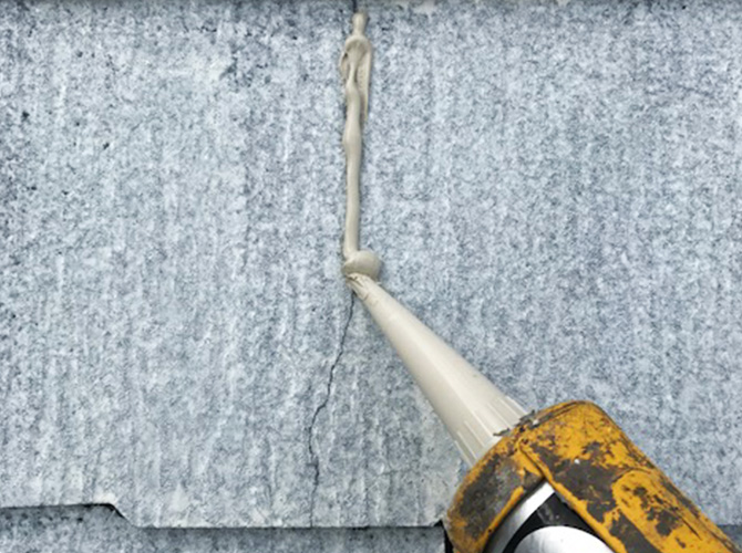 屋根材のひび割れ補修中