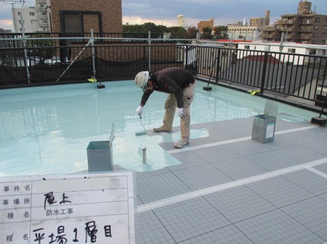 屋上のウレタン防水材一層目塗布中