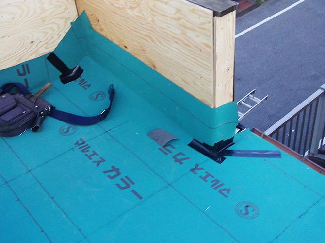 トタン屋根葺き替え工事の防水シートの設置中